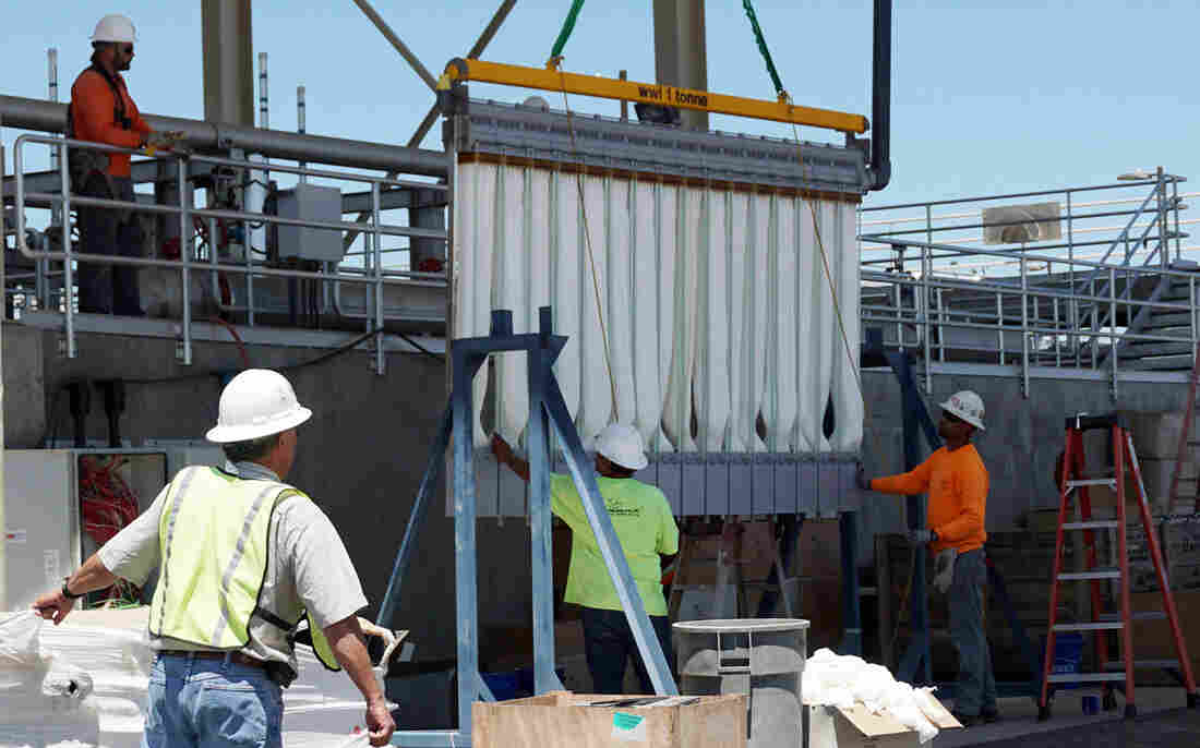 Workers install new water treatment equipment at the Modesto wastewater treatment plant, part of a $150 million upgrade.