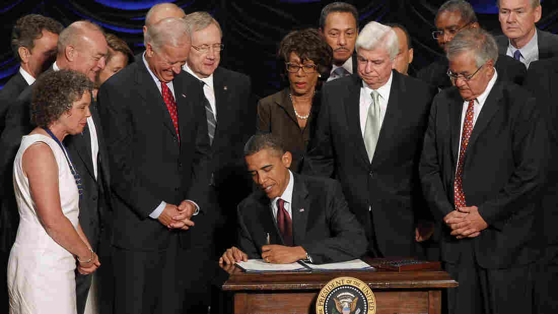 President Obama signs the Dodd-Frank financial overhaul bill in Washington on July 21, 2010. Five years later, debate over the effectiveness of the legislation continues.