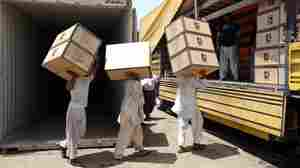 Iranian workers transfer goods from a cargo container to trucks in May at the Kalantari port in Chabahar, Iran. The removal of sanctions on Iran under a recent deal with world powers is expected to boost the country's economy, but the agreement was carefully constructed to quickly put those sanctions back in place if Iran is suspected of violations.