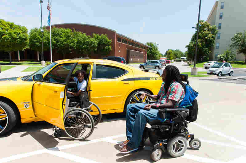 Nnaka runs into his friend Aaron Million in the parking lot of Tulsa's Center for Individuals with Physical Challenges.