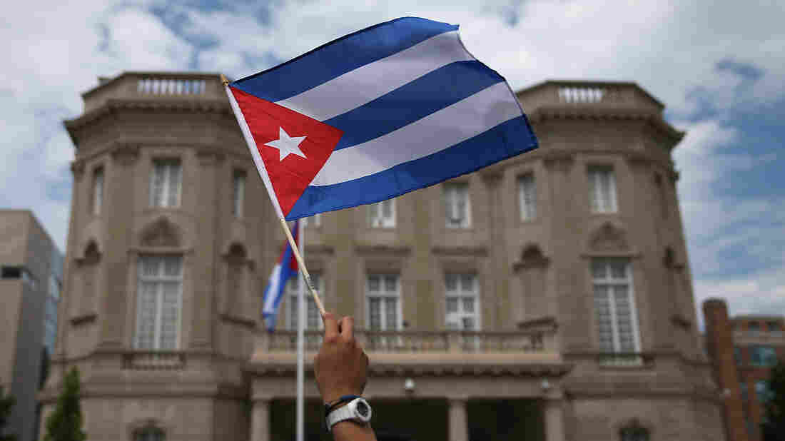 A supporter waves a Cuban flag in front of the country's embassy after it reopened for the first time in 54 years on July 20 in Washington, D.C. The embassy was closed in 1961 when U.S. President Dwight Eisenhower severed diplomatic ties with the island nation after Fidel Castro took power in a communist revolution.