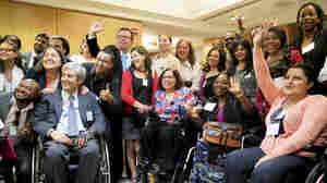 At the State Department conference for people with disabilities, adviser Judy Heumann (center) is surrounded by admirers from around the world.
