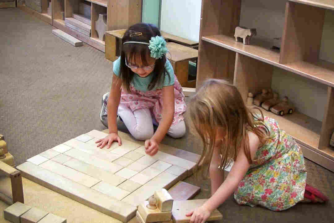 Patterns, shapes, play: Two girls work with unit blocks at Bing Nursery School.