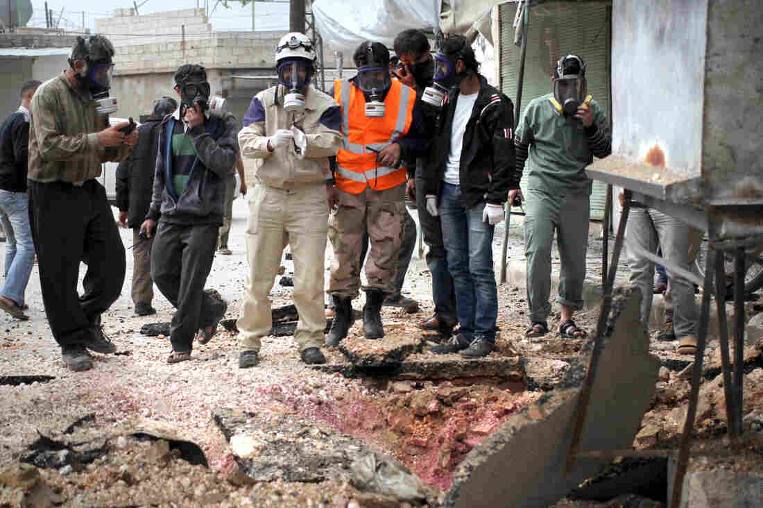 Civil defense workers wear gas masks near damaged ground in a village near the Syrian city of Idlib in May. Activists said there had been a chlorine attack.