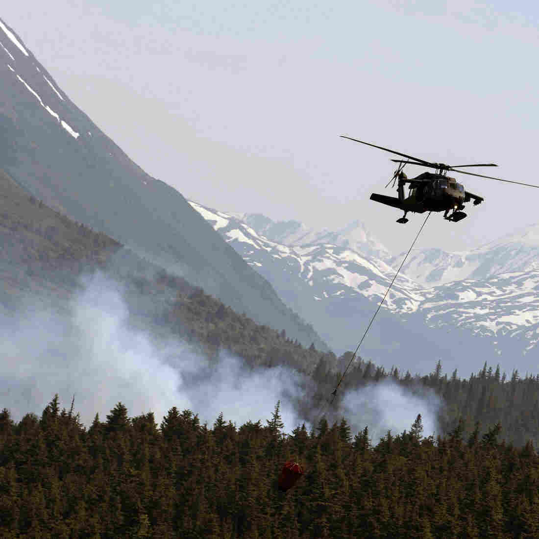 Some of Alaska's wildfires are dramatic: flames, vast plumes of smoke and firefighting battles. Here, on June 17, a helicopter releases hundreds of gallons of water onto the Stetson Creek Fire near Cooper Landing, Alaska. But even fires that look far quieter, like they're all burned out, can continue to smolder underground — and pose a dangerous threat to permafrost.