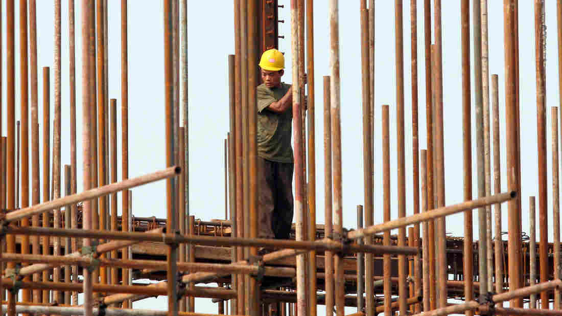 A Chinese worker is seen at a construction site in Beijing. Economic changes in China and in other places have reduced demand and prices for commodities like the metal in the building's structure.