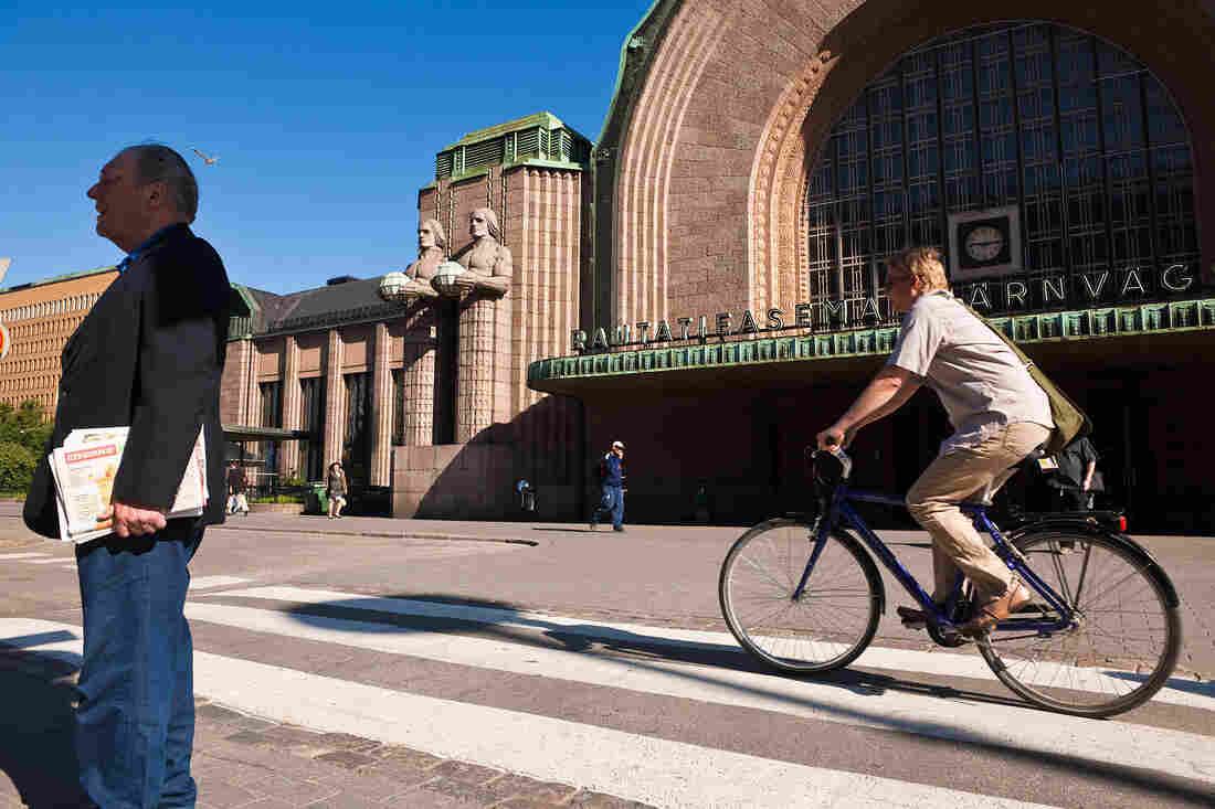 A man bikes past the Central Station in downtown Helsinki.