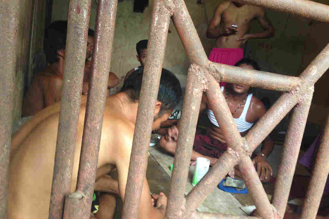 Thai and Burmese fishing boat workers sit inside a cell at the compound of a fishing company in Benjina, Indonesia on Nov. 22, 2014. The imprisoned men were considered slaves who might run away.