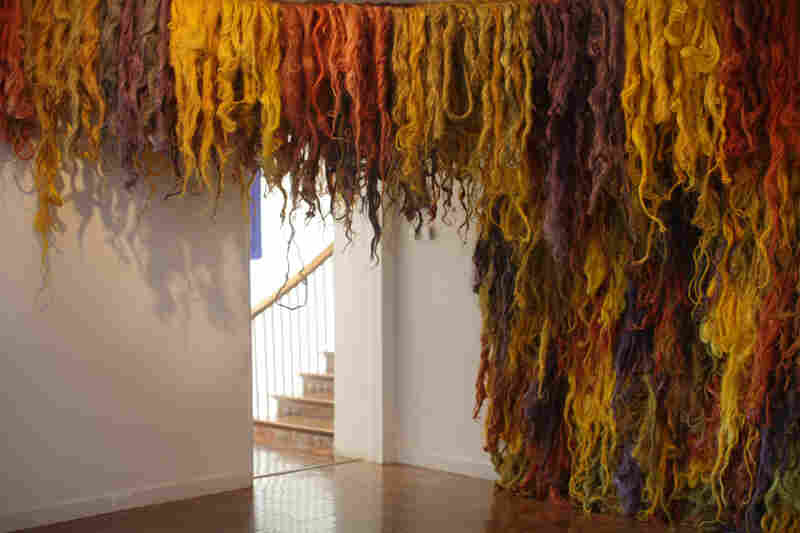 Dyed figue fibers by Susana Mejia hang in the exhibit.