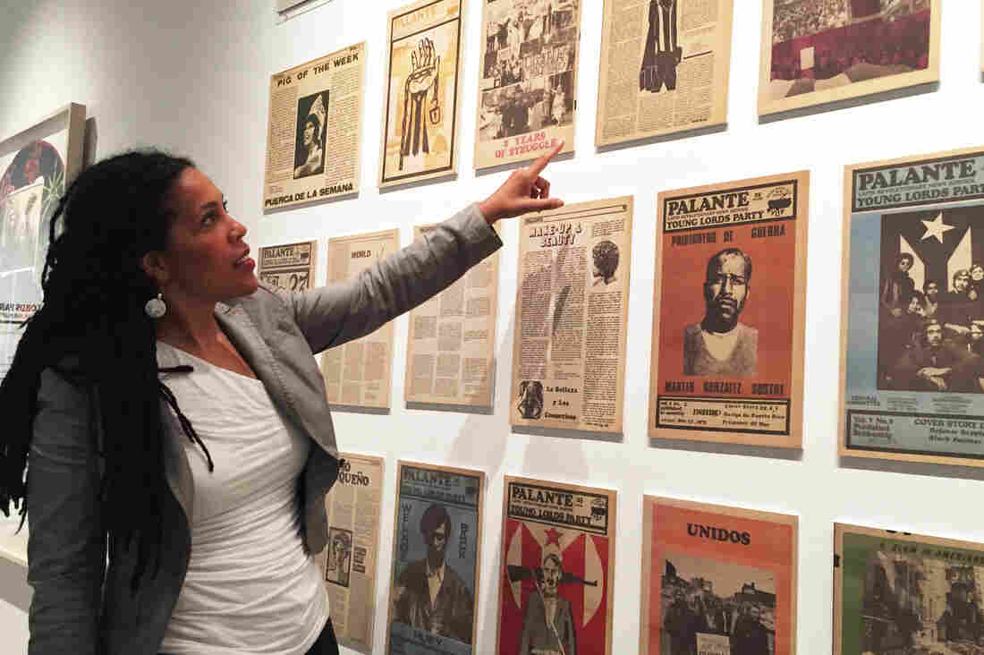 Johanna Fernández, co-curator of a new exhibition about the Young Lords, points to pages of the group's newspaper on display at the Bronx Museum of the Arts.