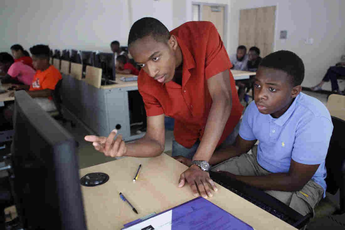 Darryl Burrell, a junior at Morgan State, helps rising seventh-grader Antonne Richardson, 11, build his 3-D ruler.