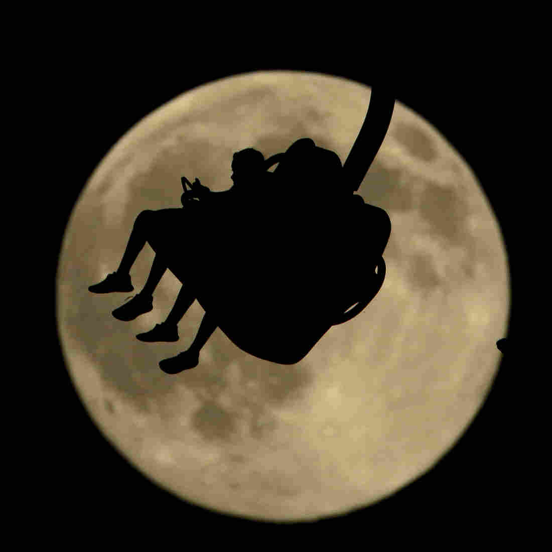 """People are silhouetted against a nearly full moon as they ride an attraction at Worlds of Fun amusement park Thursday in Kansas City, Mo. July 31 marks the second full moon of the month, a rare occurrence that has come to be known as a """"blue moon."""""""