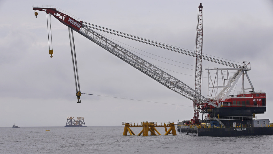 The first foundation jacket installed by Deepwater Wind in the nation's first offshore wind farm construction project is seen next to a construction crane on Monday, on the waters of the Atlantic Ocean off Block Island, R.I.
