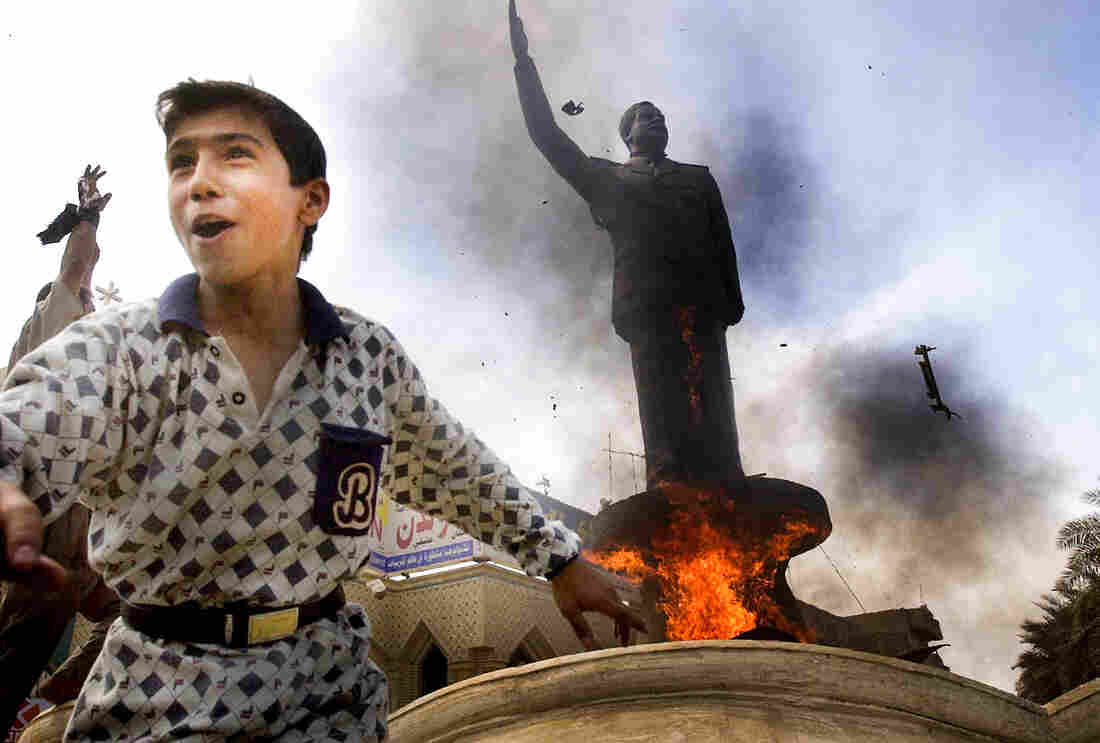 An Iraqi boy cheers as a statue of ousted Iraqi President Saddam Hussein is set ablaze during an impromptu celebration on the streets of Baghdad on April 12, 2003.