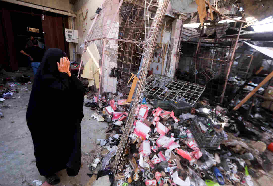 An Iraqi woman stands amid the debris following a suicide car bomb attack carried out by the Islamic State north of Baghdad, on July 18. The extremist group still holds much of western Iraq despite the U.S. air campaign that began a year ago.