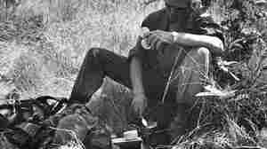 An infantryman eats food rations from cans during the Vietnam War.