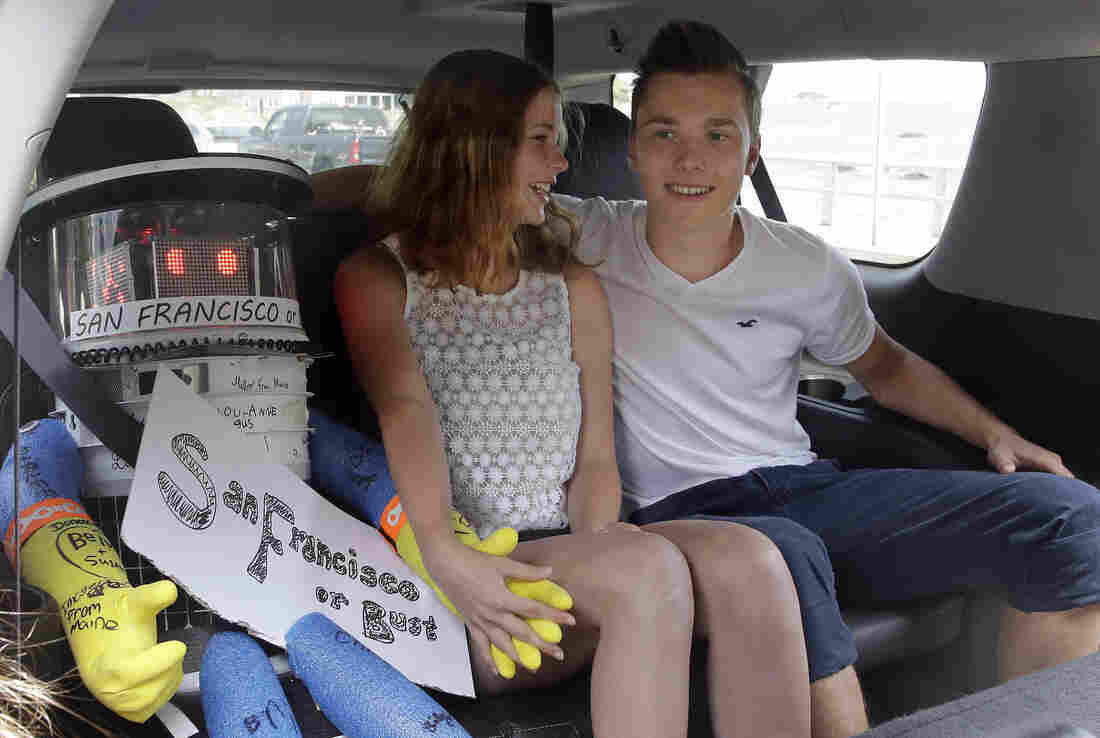 HitchBOT, a hitchhiking robot, sits with German tourists Sarah Strempel and Eric Vogel in the back seat of a vehicle as they and their companions prepare to leave Marblehead, Mass., after picking up hitchBot for its first ride on July 17.
