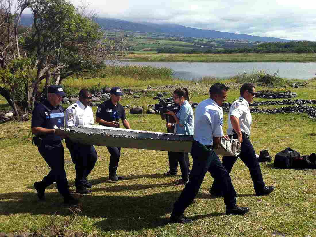 Police carry a wing fragment from the coast of Reunion island in the Indian Ocean. It was sent to France for tests.