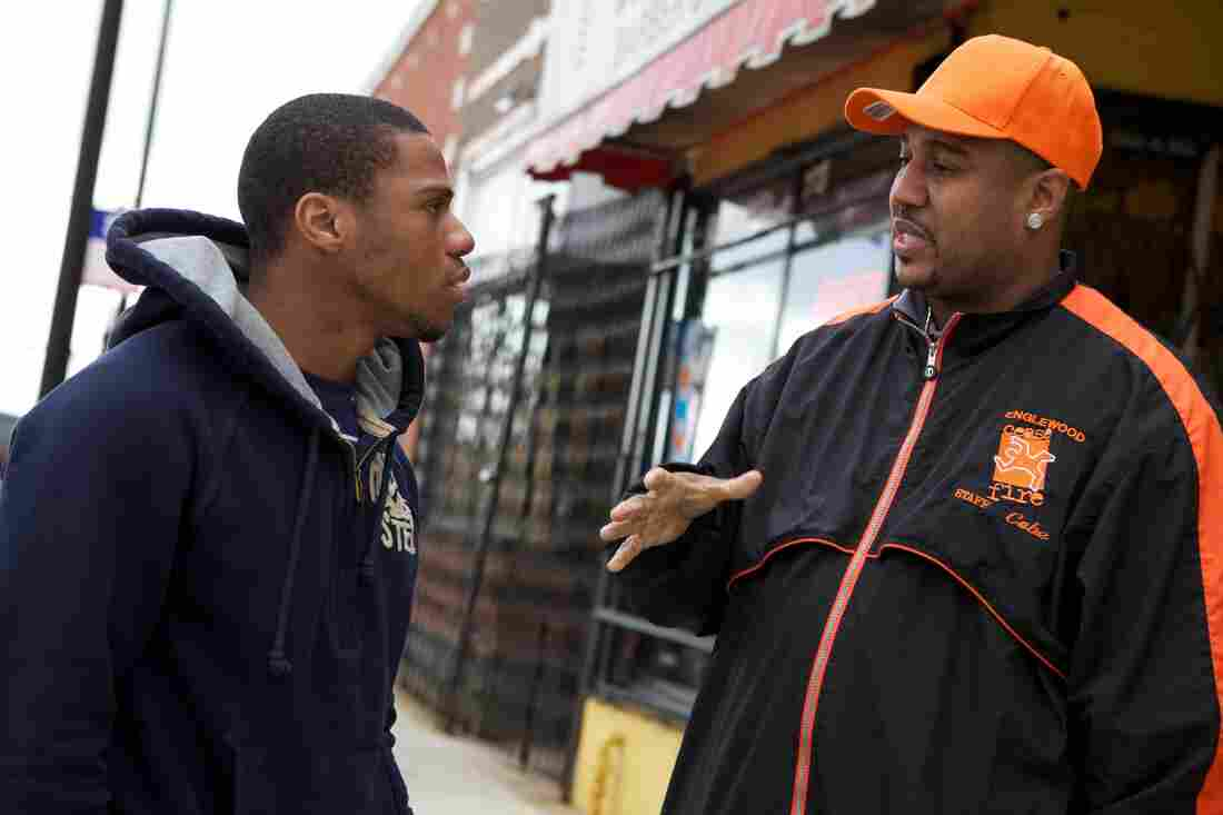 """Ricardo """"Cobe"""" Williams, wearing the cap, served time for attempted murder before joining CeaseFire as a """"violence interrupter."""" Above, he talks with Lil Mikey in a scene from the documentary The Interrupters. Lil Mikey, who'd also been in prison, went on to become an outreach worker with the organization."""