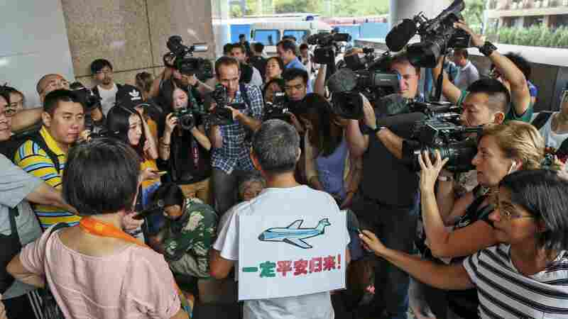 """Surrounded by journalists, a relative of passengers of Malaysia Airlines Flight 370 wears a sign reading """"Must return safely!"""" during a protest held by victims' families Thursday outside the Malaysia Airlines office in Beijing."""