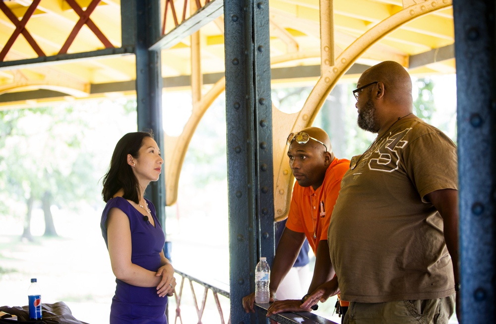 Leana Wen talks with Safe Streets outreach workers Dante Barksdale and Gardnel Carter in Druid Hill Park in Baltimore.