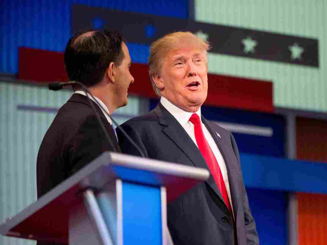Republican presidential candidates Donald Trump (right) and Wisconsin Gov. Scott Walker speak together during a commercial break at the first Republican presidential debate in Cleveland on Thursday. Trump's remarks about Fox News debate moderator Megyn Kelly have triggered a firestorm.