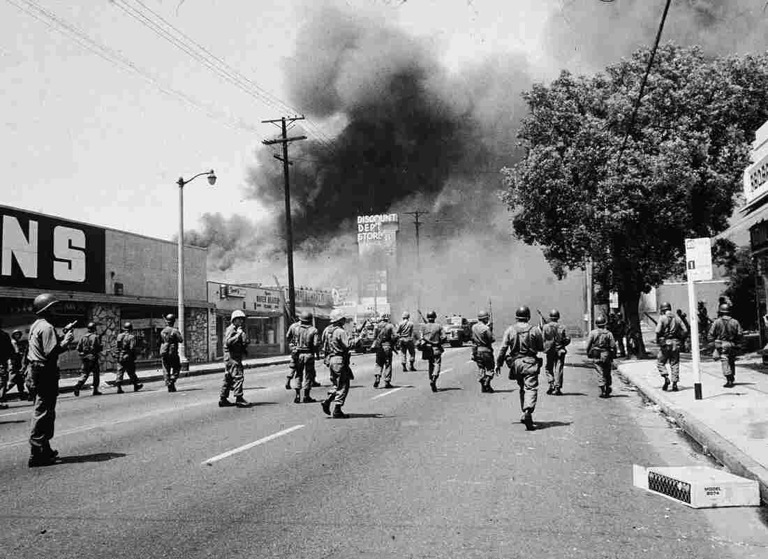 Armed National Guardsmen march toward smoke on the horizon during the street fires of the Watts Riots in Los Angeles. After six days of unrest, over a thousand people had been injured — and 34 had died.