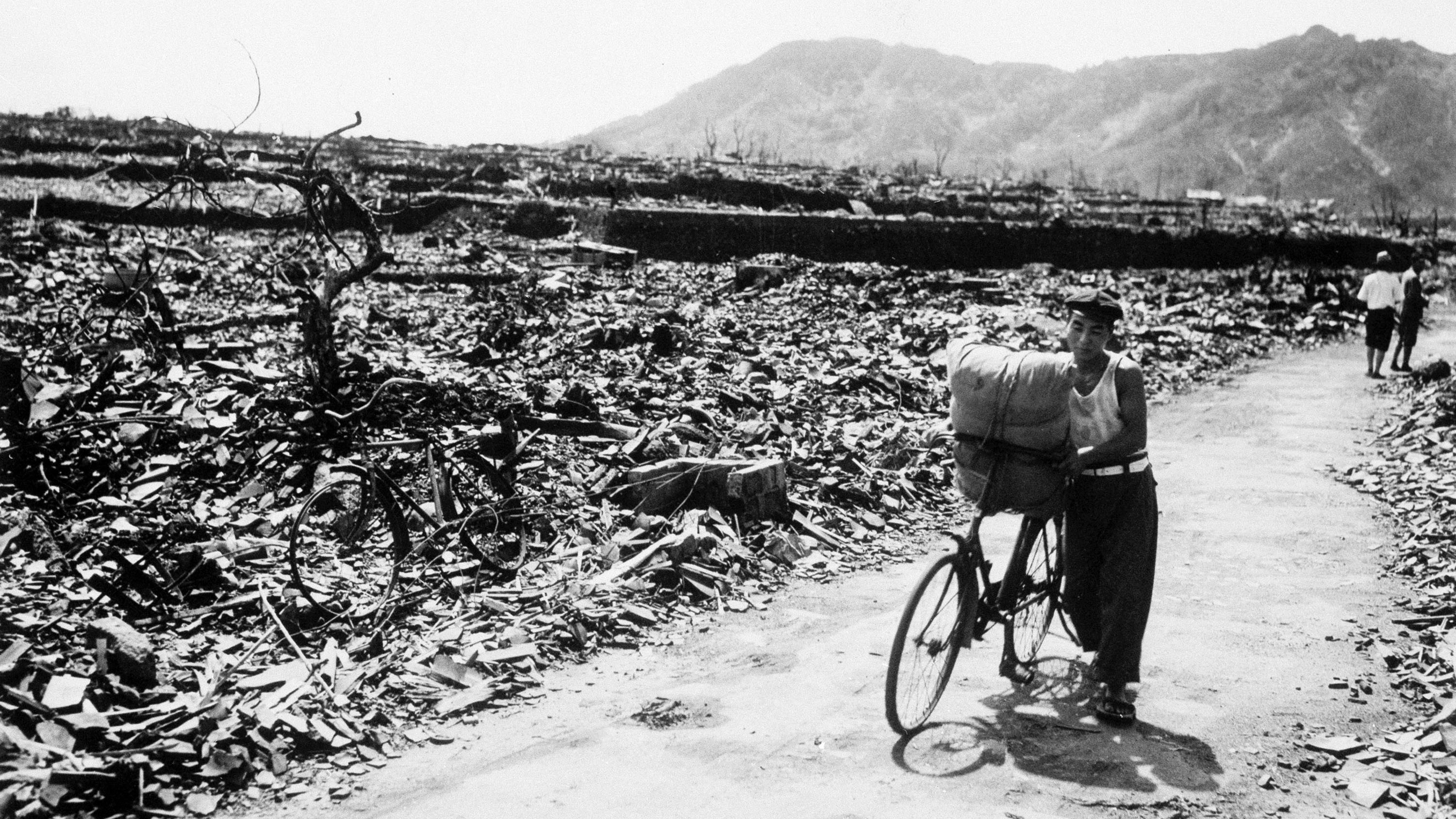 A man pushes a loaded bicycle down a cleared path in a flattened area of Nagasaki more than a month after the nuclear attack in 1945.