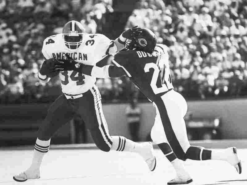 Kevin Mack of the Cleveland Browns tries to get away from the grasping hands of Dave Duerson of the Chicago Bears during Pro Bowl in Honolulu, 1988.