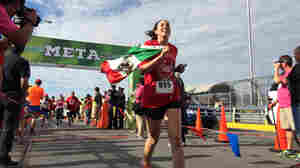 Stephanie Acosta of El Paso, Texas, crosses the finish line after running a 10K race from the United States into Mexico.