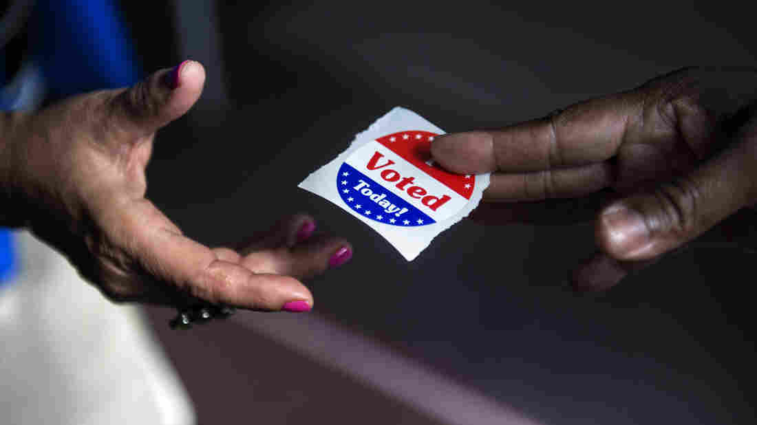 """A poll worker hands out """"I Voted Today"""" stickers in Washington, D.C., in 2012. Journalist Ari Berman says a 2013 Supreme Court ruling opened the door for new voting restrictions that  disproportionately affect poor people, young people and people of color."""