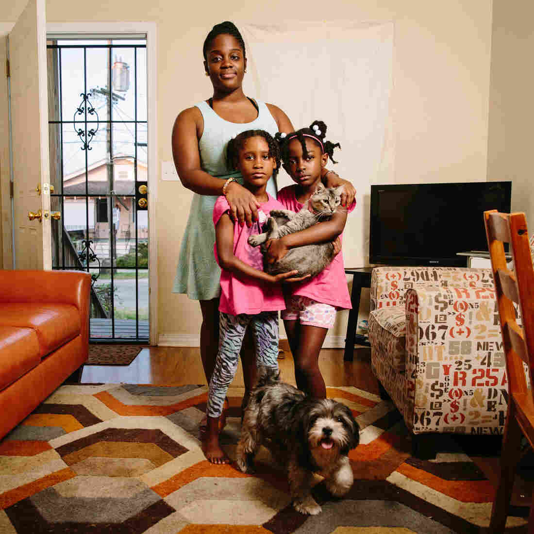 """Dyha Gresham (front, left), her older sister Briceshanay (in back) and Briceshanay's daughter Uri stand in their New Orleans home with the family's cat Sugar-Pepper and dog Selena. After Katrina, Briceshanay says, she relied on theater and the arts to help her """"move through terrible and difficult times."""""""
