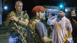 Members of the Oath Keepers walk with their personal weapons on the street during protests in Ferguson, Mo., early Tuesday morning.