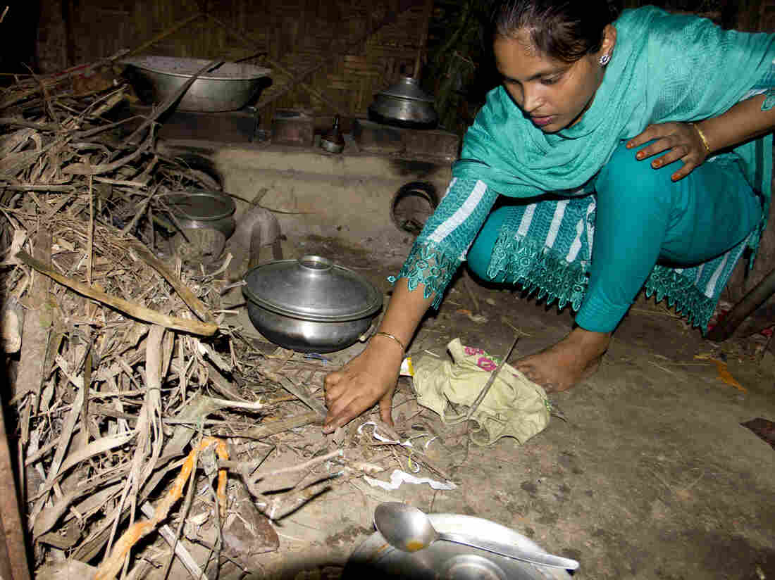 Minu gathers sticks to place under the burner in her parent's home in the village.