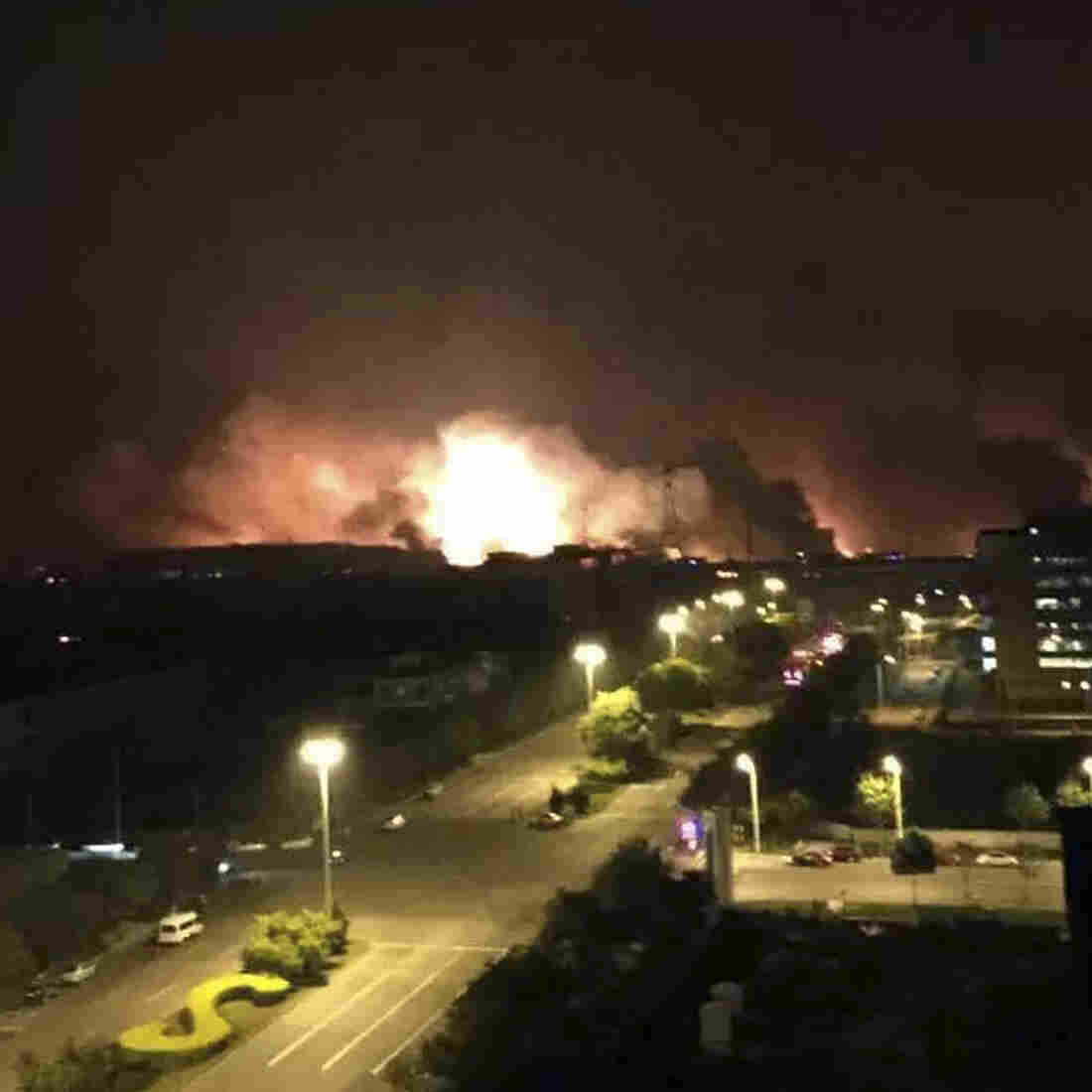 In this photo released by Xinhua News Agency smoke and fire erupt into the night sky after an explosion in north China's Tianjin Municipality early Thursday Aug. 13 local time.