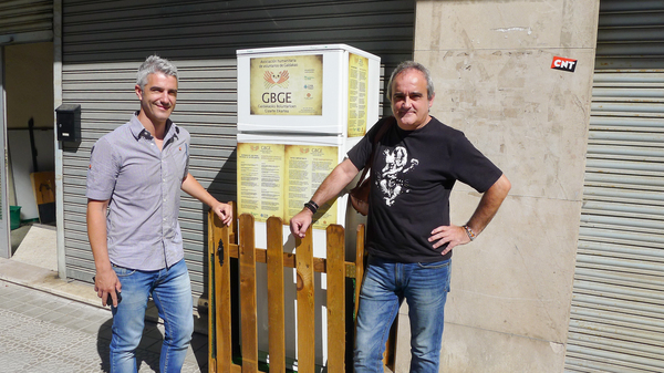 Galdakao Mayor Ibon Uribe (left) and volunteer Javier Goikoetxea pose in front of the Solidarity Fridge, Spain's first communal refrigerator, shared by citizens in Galdakao, a city outside Bilbao.