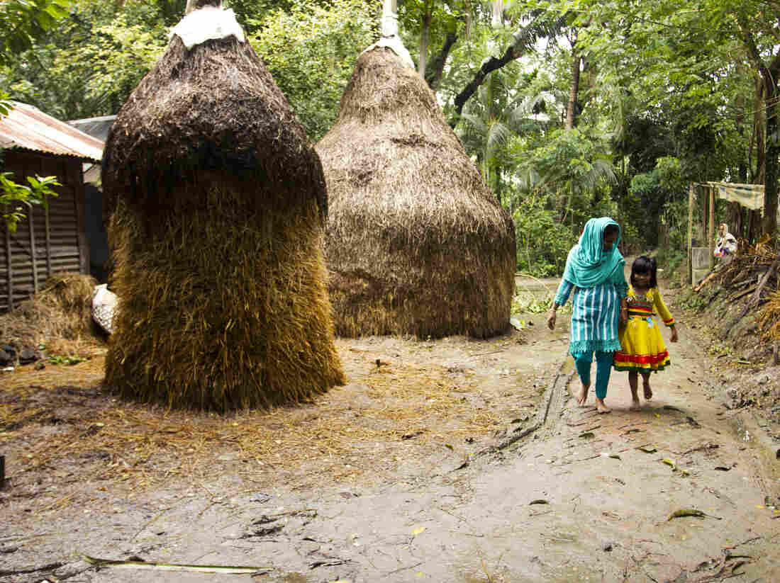 Minu in the village with 7-year old daughter, Sumaiya. Sumaiya lives here with Minu's parents.