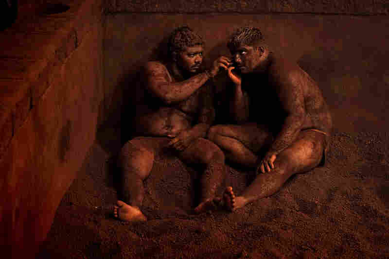 Merit Winner: They're clad in a loincloth. And they're in a pit made of clay. The men are participants in the traditional Indian wrestling called Kushti. After a session, wrestlers rest against the walls of the arena, covering their heads and bodies with earth to soak up any perspiration.