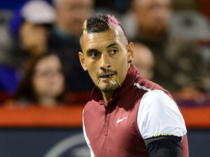 Tennis bad boy Nick Kyrgios bites his chain during his Rogers Cup match against Stan Wawrinka.