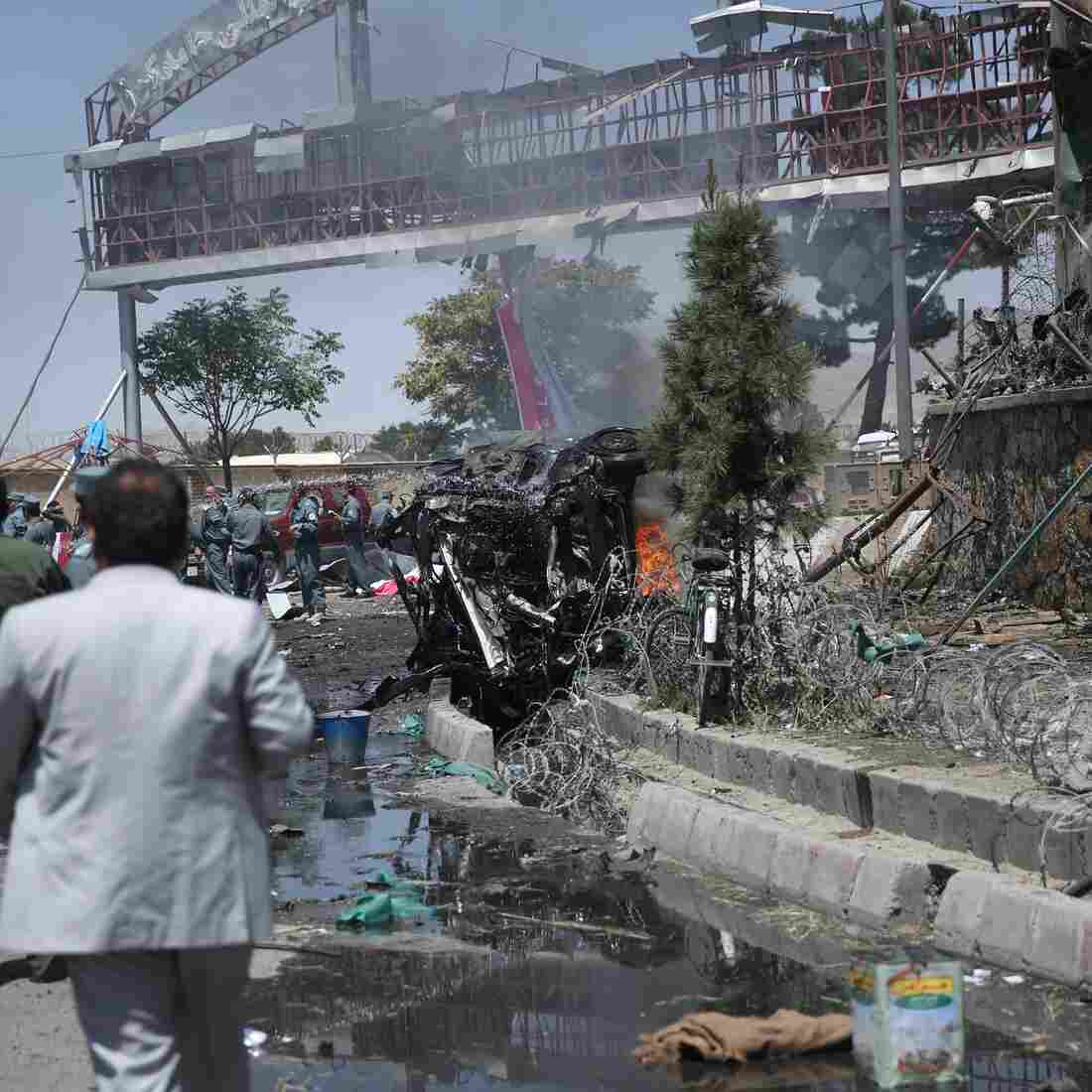 Afghan security forces inspect a suicide bombing attack on Aug. 10 near the main gate of Kabul's international airport. It was one of a series of recent attacks in the Afghan capital that have left at least 50 dead. Violence in Afghanistan has increased since U.S. combat troops pulled out last year.