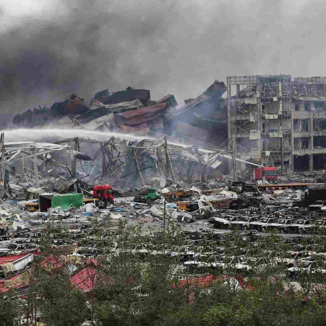 Firefighters work at the warehouse explosion site in Tianjin, north China, Friday. Scorched cars are in the foreground; toppled shipping containers are in the background.