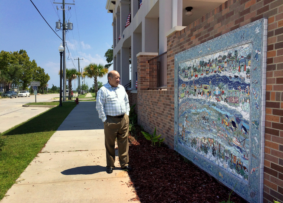 Mayor Mike Smith stands near a mural, created by residents, that depicts Waveland before and after Katrina. (Evelina Burnett/MPB)