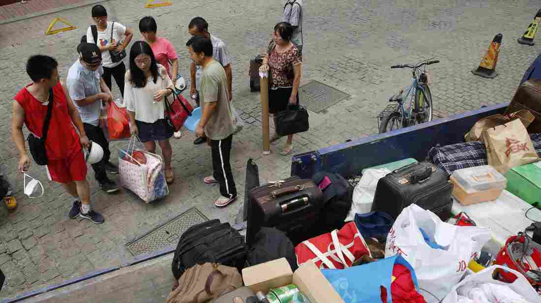 People carry their luggage as they are evacuated Saturday in the aftermath of a huge explosion that rocked the port city of Tianjin, China.