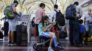 Alisha Lalani, 10, of Ft. Lauderdale, Fla., looks at her phone as her mother and brother check in for their flight to Miami at Washington's Reagan National Airport. Their flight was one of thousands delayed as a result of a technical glitch with an FAA automated system.