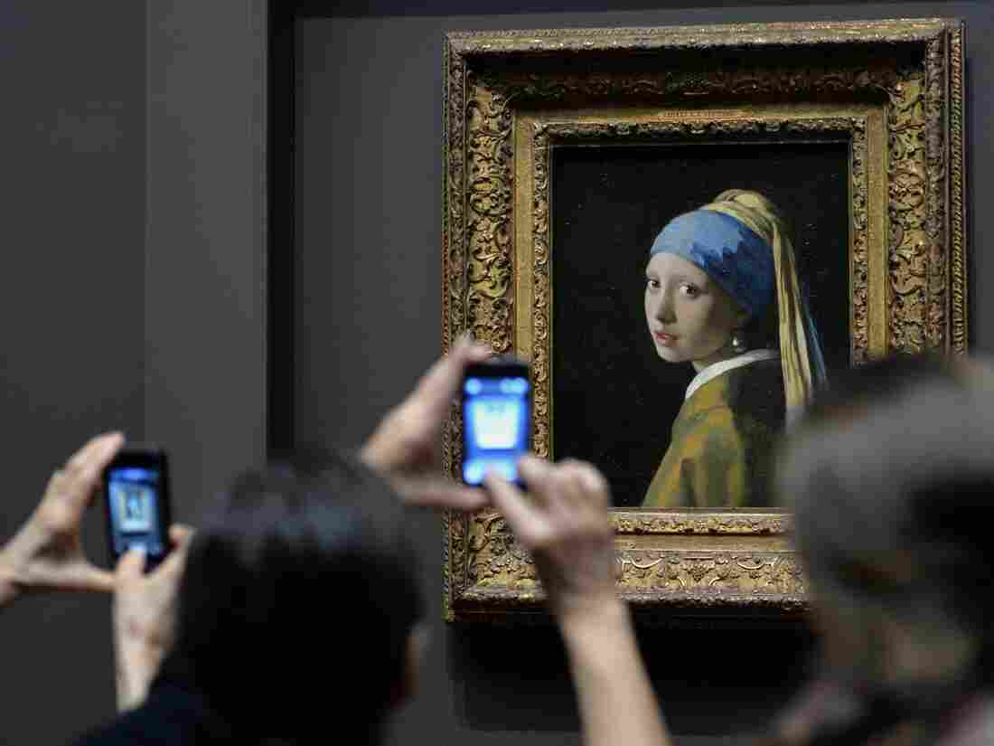"""Vermeer's Girl with a Pearl Earring stares back at cellphones at the Frick Collection in New York City. """"The art museum used to offer objects, works of art, the finest that we have,"""" Lewis says. """"And it's gone from offering objects to offering an experience."""""""