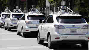 A row of Google self-driving Lexus cars at a Google event in Mountain View, Calif. The cars use sensors and computing power to maneuver around traffic.