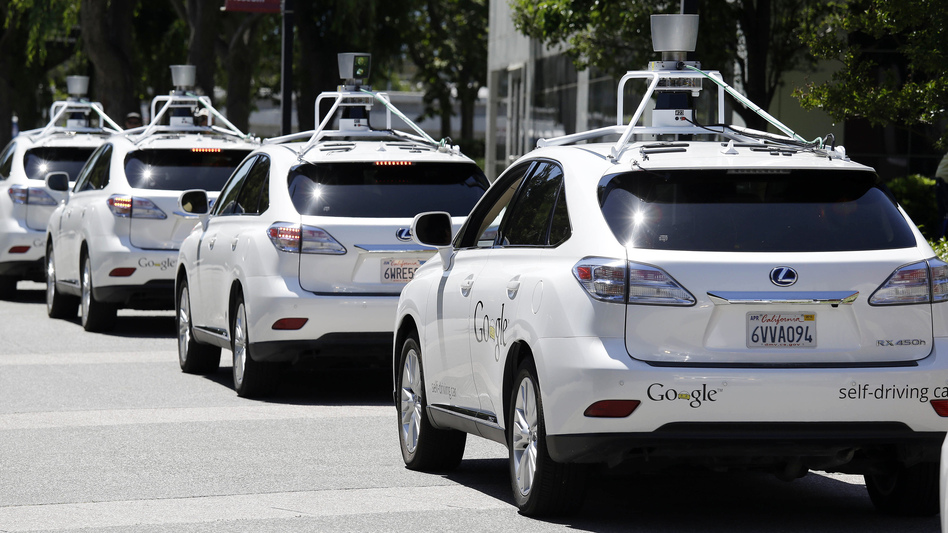 A row of Google self-driving Lexus cars at a Google event in Mountain View, Calif. The cars use sensors and computing power to maneuver around traffic. (Eric Risberg/AP)