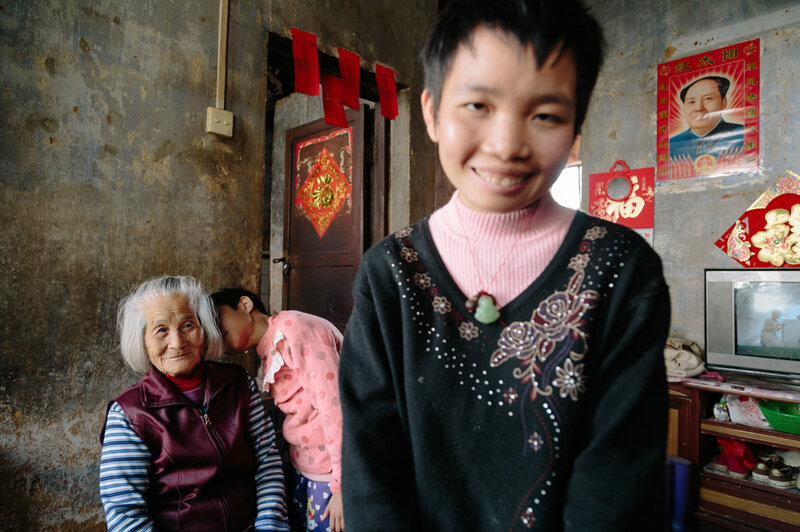 Mei Lin, who's 83, enjoys a moment with her two granddaughters, both of whom are mentally ill.