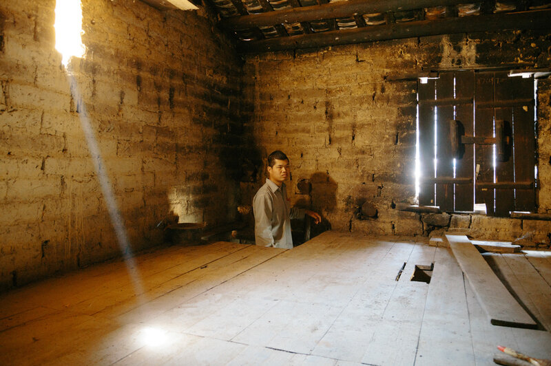 Jiagui Su, 33, stands on a ladder to the loft in his parents' house. He's lived with them since he was diagnosed with schizophrenia 10 years ago.