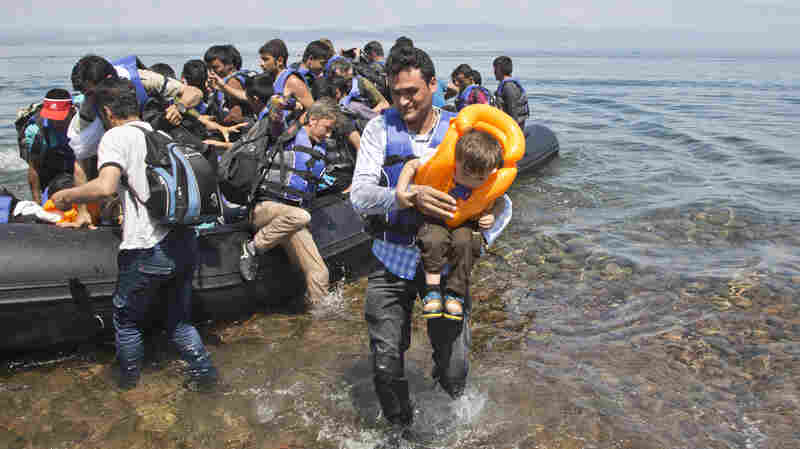 A migrant arrives with his son on the shore near the village of Skala Sikaminea, on the southeastern Greek island of Lesbos, Greece on Friday. Greece this year has been overwhelmed by record numbers of migrants arriving on its eastern Aegean islands, with more than 160,000 landing so far. [Caption from AP, lightly edited.]